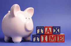 Pink Piggy Bank with Tax Time building block letters Royalty Free Stock Photo