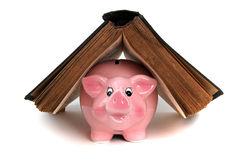 Pink piggy bank under old book Royalty Free Stock Image