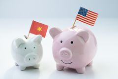 Pink piggy bank with USA national flag standing with small white one with China flag on white background, metaphor of US and China. Finance, economics or trade royalty free stock image