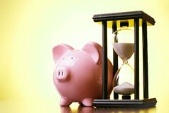 Pink piggy bank with a vintage hourglass behind Stock Photos