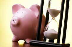 Pink piggy bank with a vintage hourglass behind Stock Images
