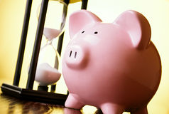 Pink piggy bank with a vintage hourglass behind Stock Image