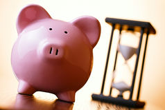 Pink piggy bank with a vintage hourglass behind Stock Photography