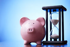 Pink piggy bank with a vintage hourglass behind Royalty Free Stock Photos