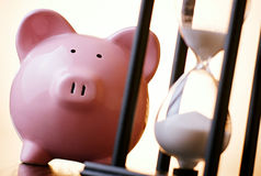 Pink piggy bank with a vintage hourglass behind Stock Photo
