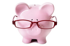 Pink piggybank wearing glasses isolated on white background, front view, savings wisdom Royalty Free Stock Photos