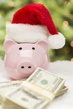 Pink Piggy Bank Wearing Santa Hat Near Stacks of Money on Snowfl Royalty Free Stock Photo
