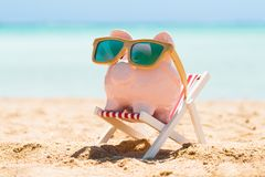 Piggy Bank With Wooden Sunglasses On The Deck Chair. Pink Piggy Bank Wearing Wooden Sunglasses Kept On The Deck Chair At Beach stock images