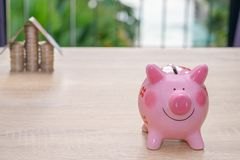Pink piggy bank on wooden desk - save money to buy house concept Stock Photography