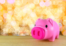 Pink piggy bank on wooden table Stock Image