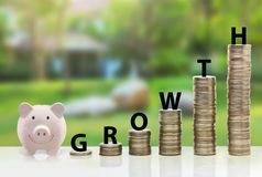 Pink piggy ceramic bank with rising golden coins, growth money. Saving royalty free stock photos