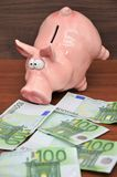 Pink piggy coin bank with 100 euro notes royalty free stock photos