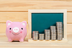Pink piggy save money. Pink piggy save money and coin in blank chalkboard on wooden room Stock Image
