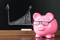 Pink piggybank with glasses on desk Stock Photo