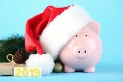 Piggybank in santa hat. Pink piggybank in santa hat with inscription 2019 on blue background royalty free stock photo