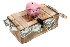 Pink piggybank on wooden case with dollar notes Royalty Free Stock Photos