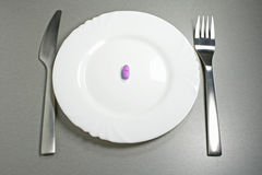 Pink pill breakfast. Pink pill with fork and knife on a white plate Stock Images