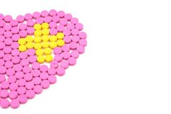 Pink pill is heart shaped and Yellow pills are placed in a cross shape. Creative healthcare and medicine concept. Isolated on white background Stock Photo