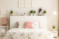 Pink pillow on bed with headboard in white bedroom interior with plants and posters. Real photo Stock Photos