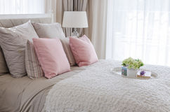 Pink pillows on bed with white tray of flower Stock Photos