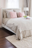 Pink pillows on bed with white tray of flower at home Stock Photo
