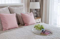 Pink pillows on bed with white tray of flower Royalty Free Stock Image