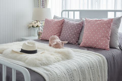 Pink pillows with pink doll on white wooden bed and classic hat Stock Photo