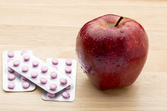 Pink pills blister pack and fresh red apple Stock Image
