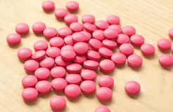 Pink pills on brown background Royalty Free Stock Photos