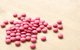 Pink pills on brown background Stock Image