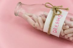 Pink pills in the `Dreams` bottle. Concepts - hope in medicine, illusion, dependence, get away from reality,  the danger of the drug proposed as `good Stock Image
