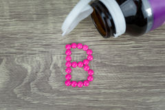 Pink pills forming shape to B alphabet on wood background Royalty Free Stock Photography