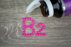 Pink pills forming shape to B2 alphabet on wood background Royalty Free Stock Images