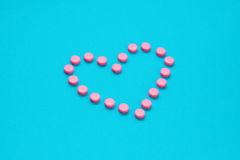 Pink Pills In Heart Shape  on Blue background Stock Photography