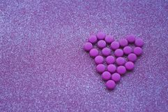 Pink pills laid out in shape of a heart on glitter pink background. stock photos