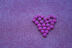 Pink pills laid out in shape of a heart on glitter pink background. royalty free stock images
