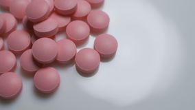 Pink pills rotate on a white background. Concept - medicine, production of drugs, vitamins, antibiotics stock video