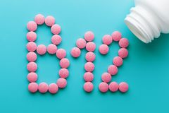 Pink pills in the shape of the letter B12 on a blue background, spilled out of a white can. Concept of dietary supplements stock photography