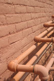 Pink Pipes. Pipes against an old exterior wall royalty free stock image