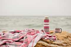 Pink plaid in a cage and a thermos with a cup on a stone on the Stock Photo
