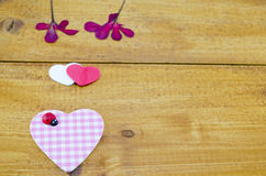 Pink plaided heart and some dried flowers. On a wooden table Royalty Free Stock Photos