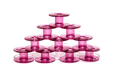 Pink plastic bobbin for sewing machine. On white background Royalty Free Stock Photos