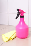 Pink plastic bottle of cleaning product and duster on tiled floo Royalty Free Stock Photos