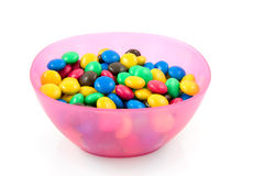 Pink plastic bowl with chocolate candy Royalty Free Stock Photos