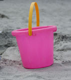 Pink Plastic Bucket in the Sand. A pink bucket in the sand, a child's toy for the beach stock photo