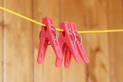 Pink plastic clothespins hanging on a rope yellow royalty free stock photo