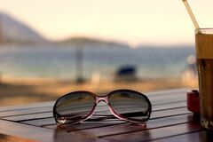 Pink Plastic Framed Wayfarer Sunglasses on Brown Table Top Royalty Free Stock Image
