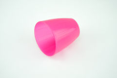 Pink plastic mug on white background. Isolated royalty free stock image
