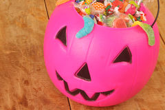 Pink plastic pumpkin filled with candy Royalty Free Stock Photos