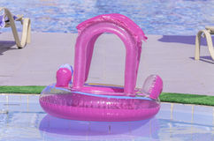 Pink plastic ring floating in a pool Royalty Free Stock Photography